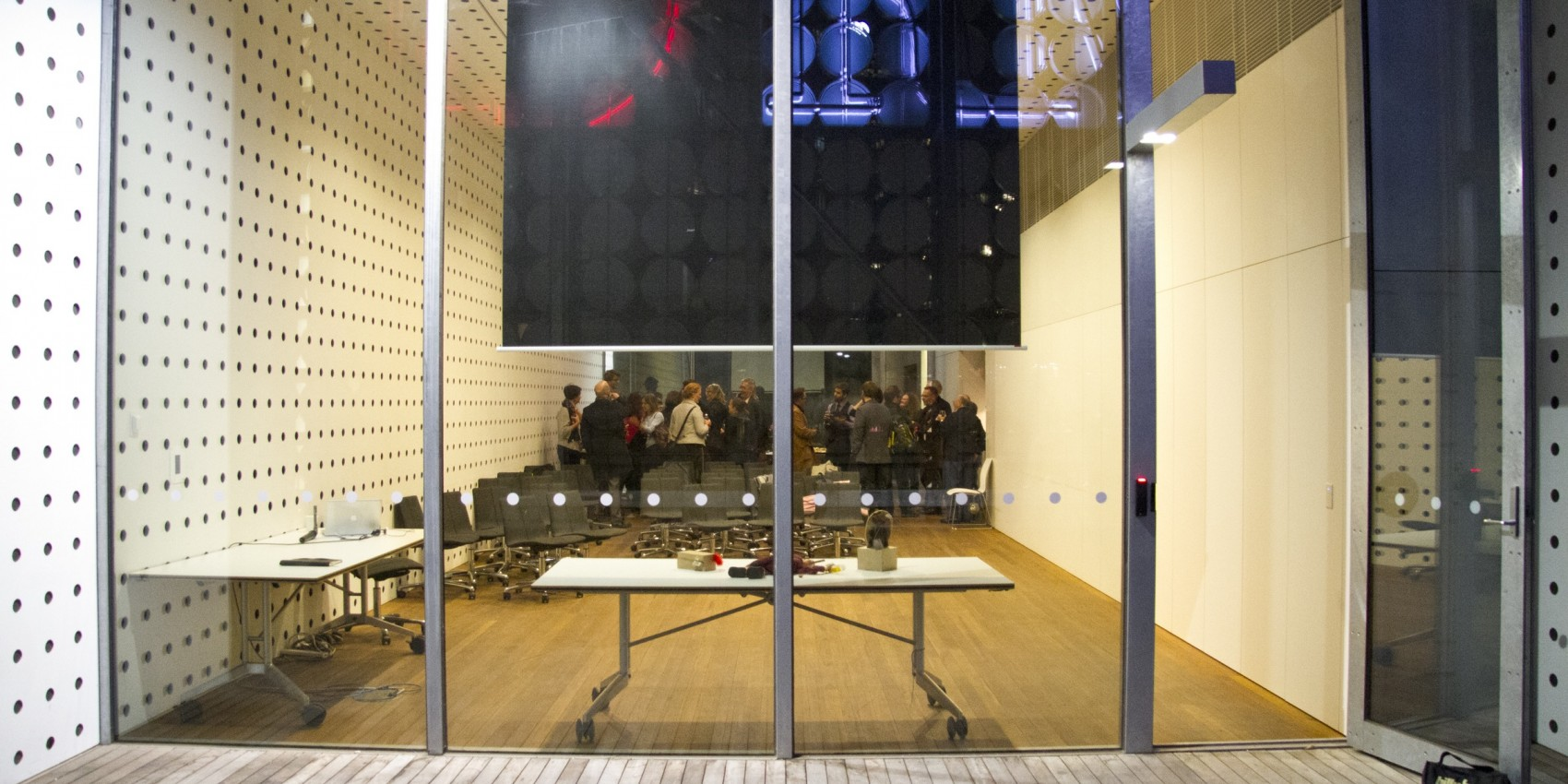 Looking through glass doors at a room where many people are gathered
