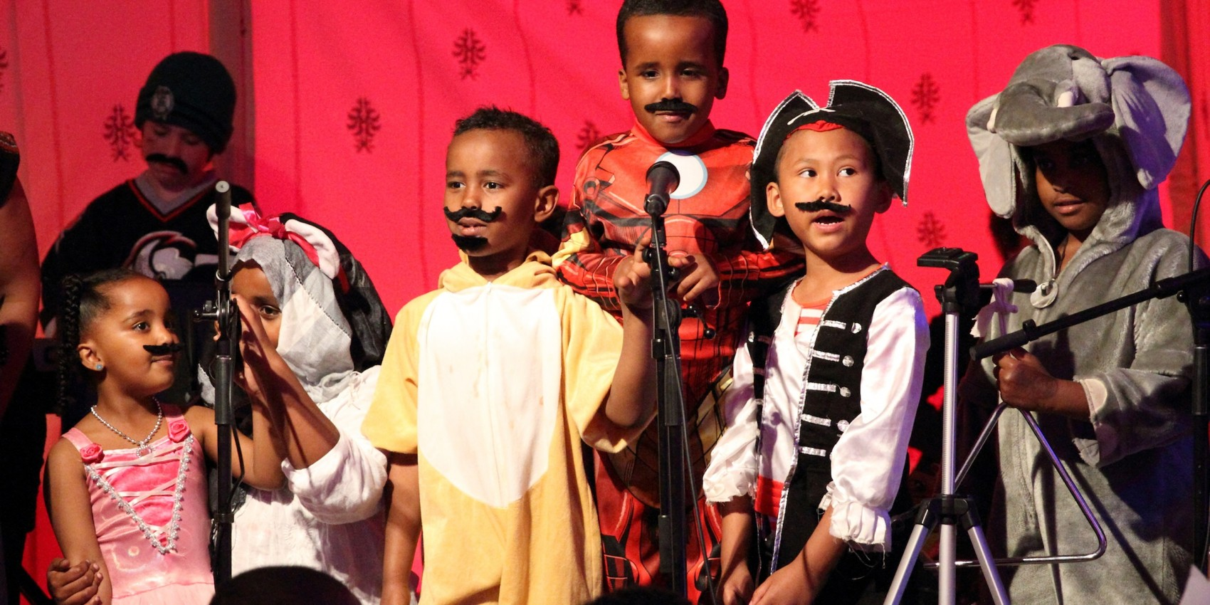 Seven young children in dress ups in a performance space with microphones