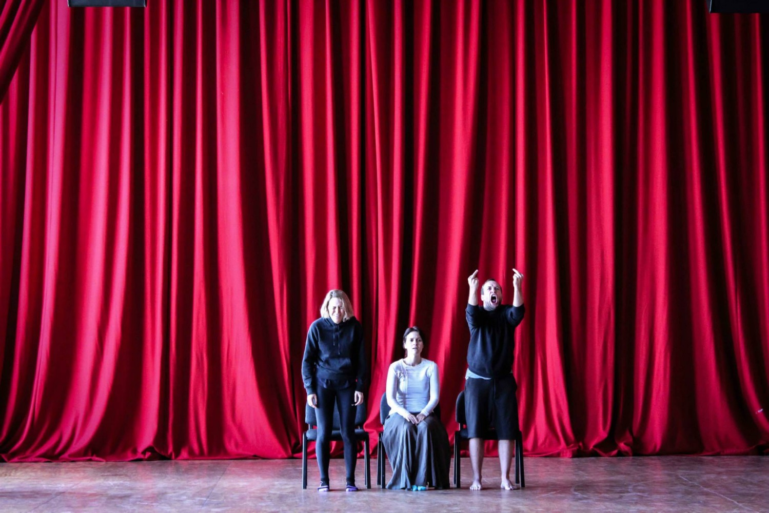 Two standing and one seated performers in a space in front a large red curtain