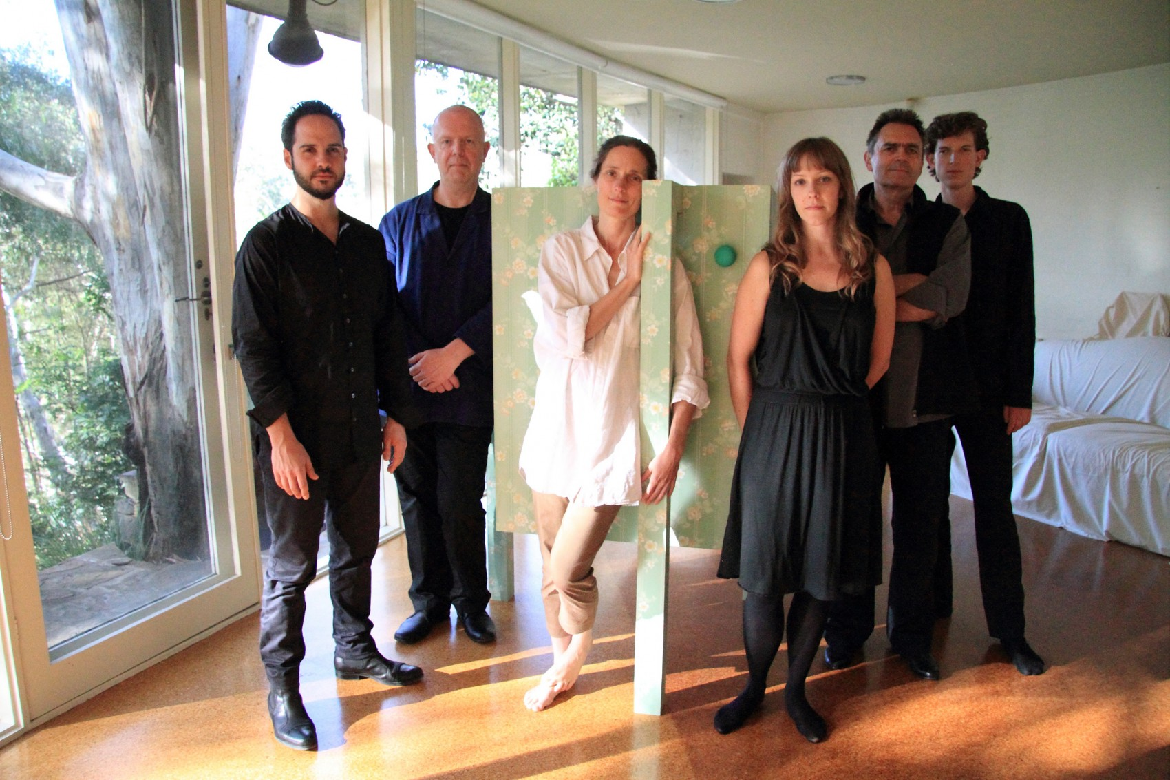 Six people standing in a sunny room around a pale green box on a stand