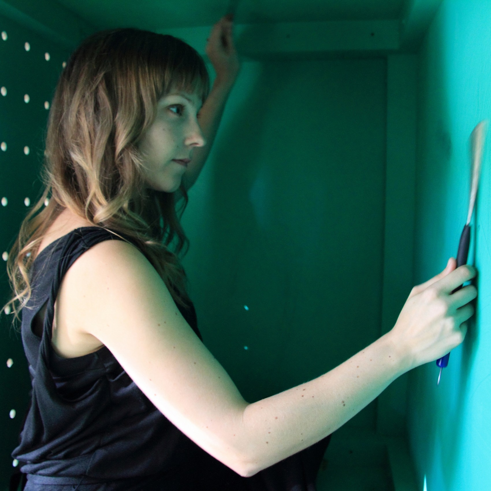 Side image of woman wearing black singlet using a small hand tool on a white wall