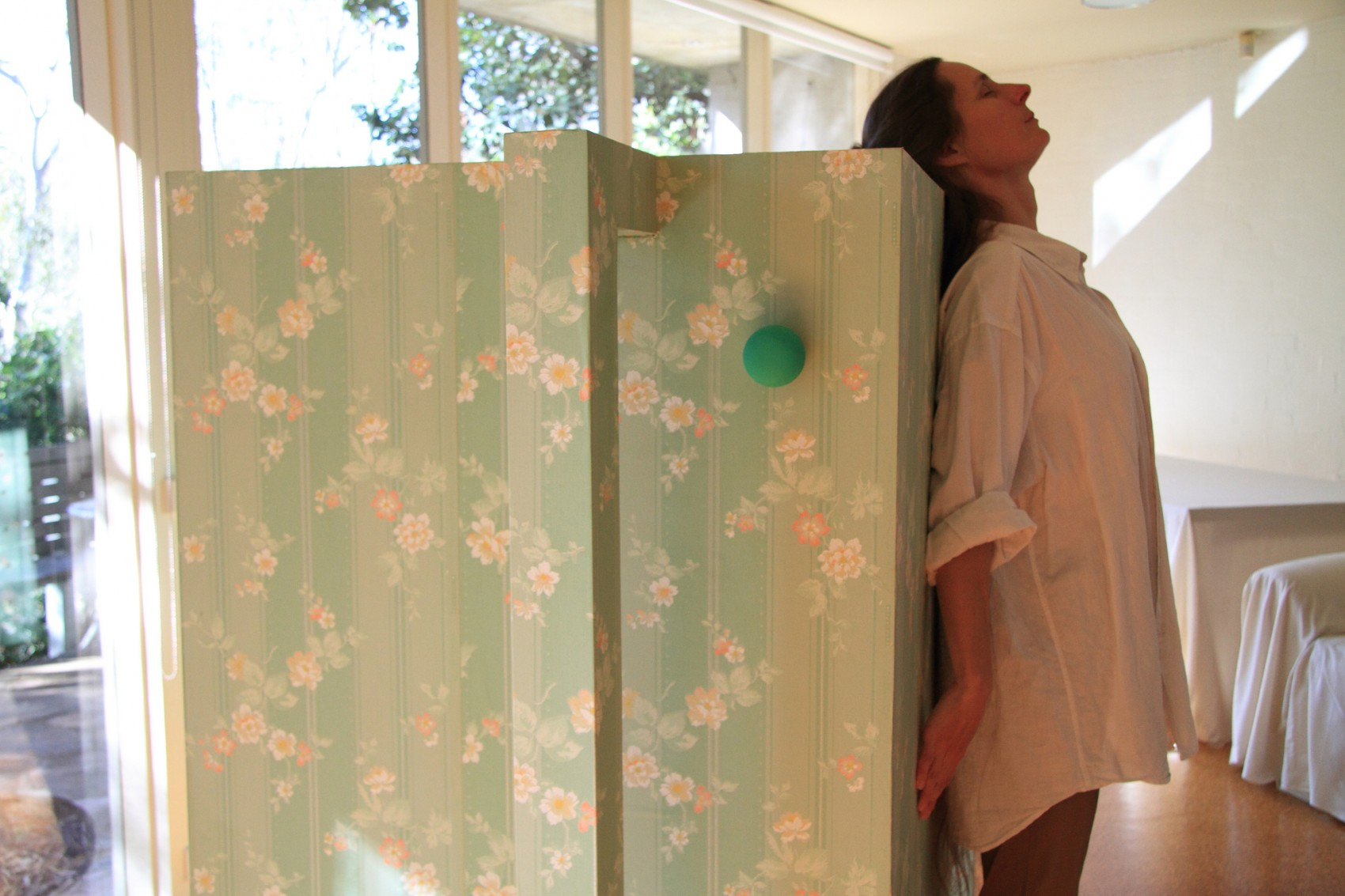 Woman in a sunny room standing with her back against a pale green floral patterned box