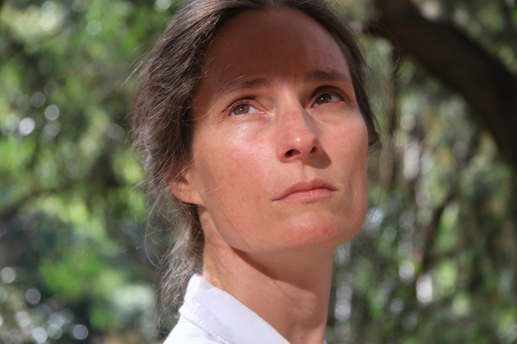 Close shot of woman's face outside in dappled light with tree foliage behind her