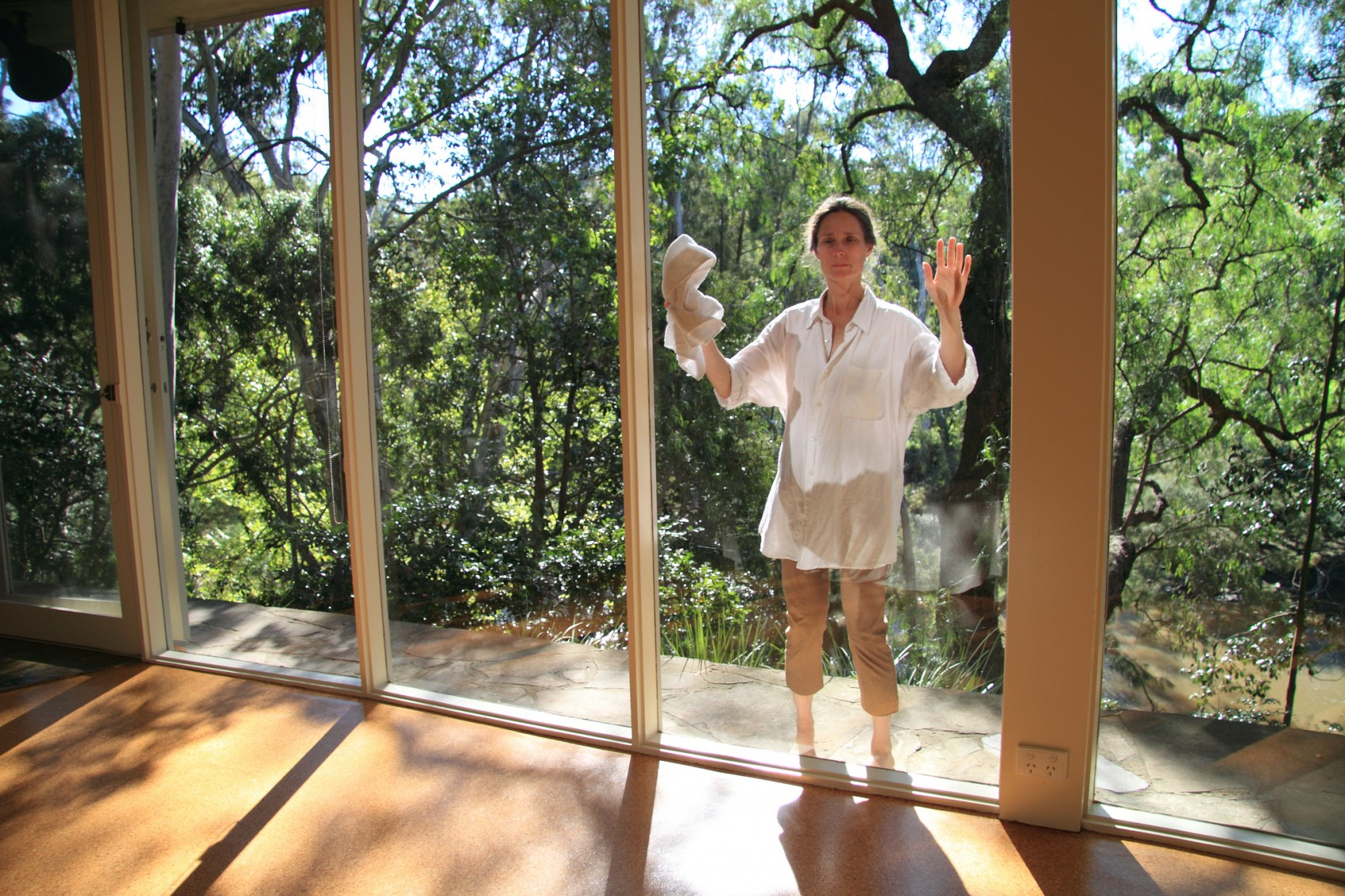 Woman wearing white shirt with arms raised and pressed against long window with tree foliage and blue sky behind her