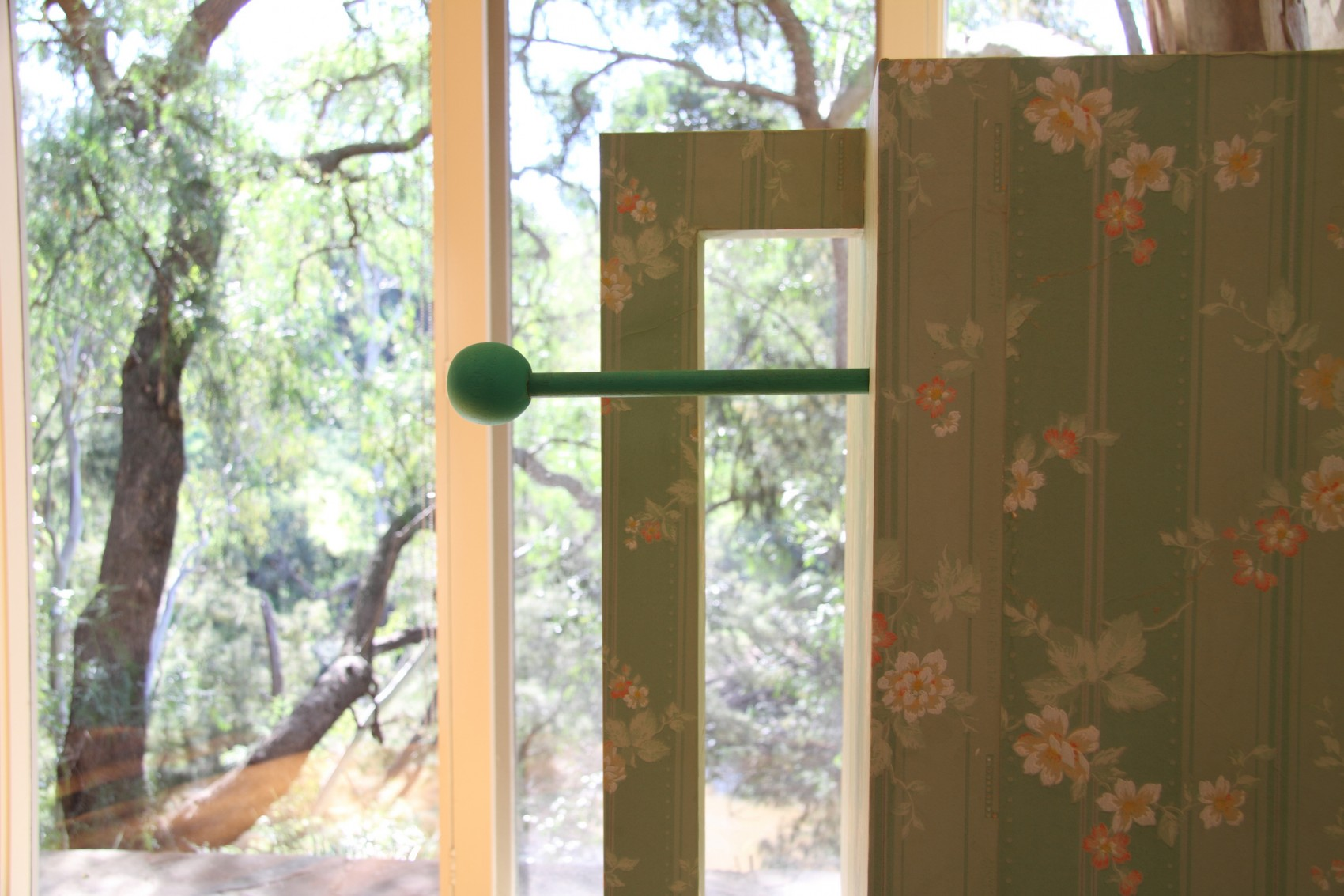 Pale green floral patterned box next to a window through which we see tree foliage