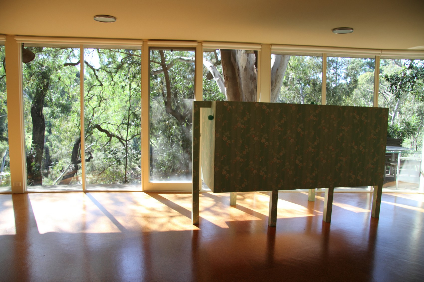 Pale green floral patterned box in a large sunny room with tree foliage visible through window