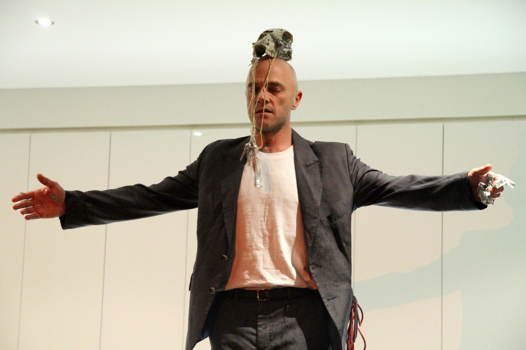 Man with outstretched arms and eyes closed, balancing a skull on his head