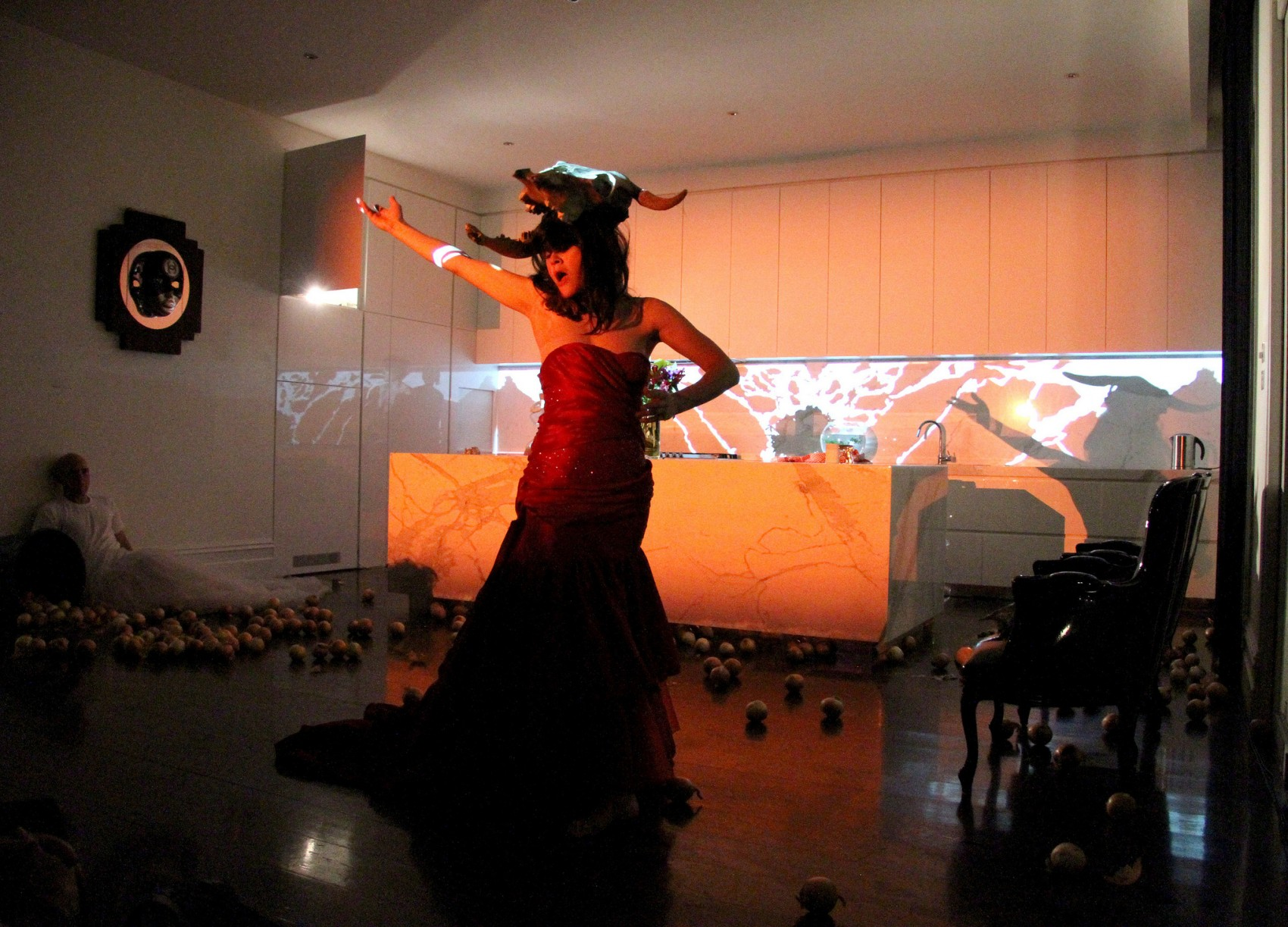 A woman wearing a red dress and an animal mask on her head strikes a dramatic pose in a kitchen where a man is slumped on the floor against a wall