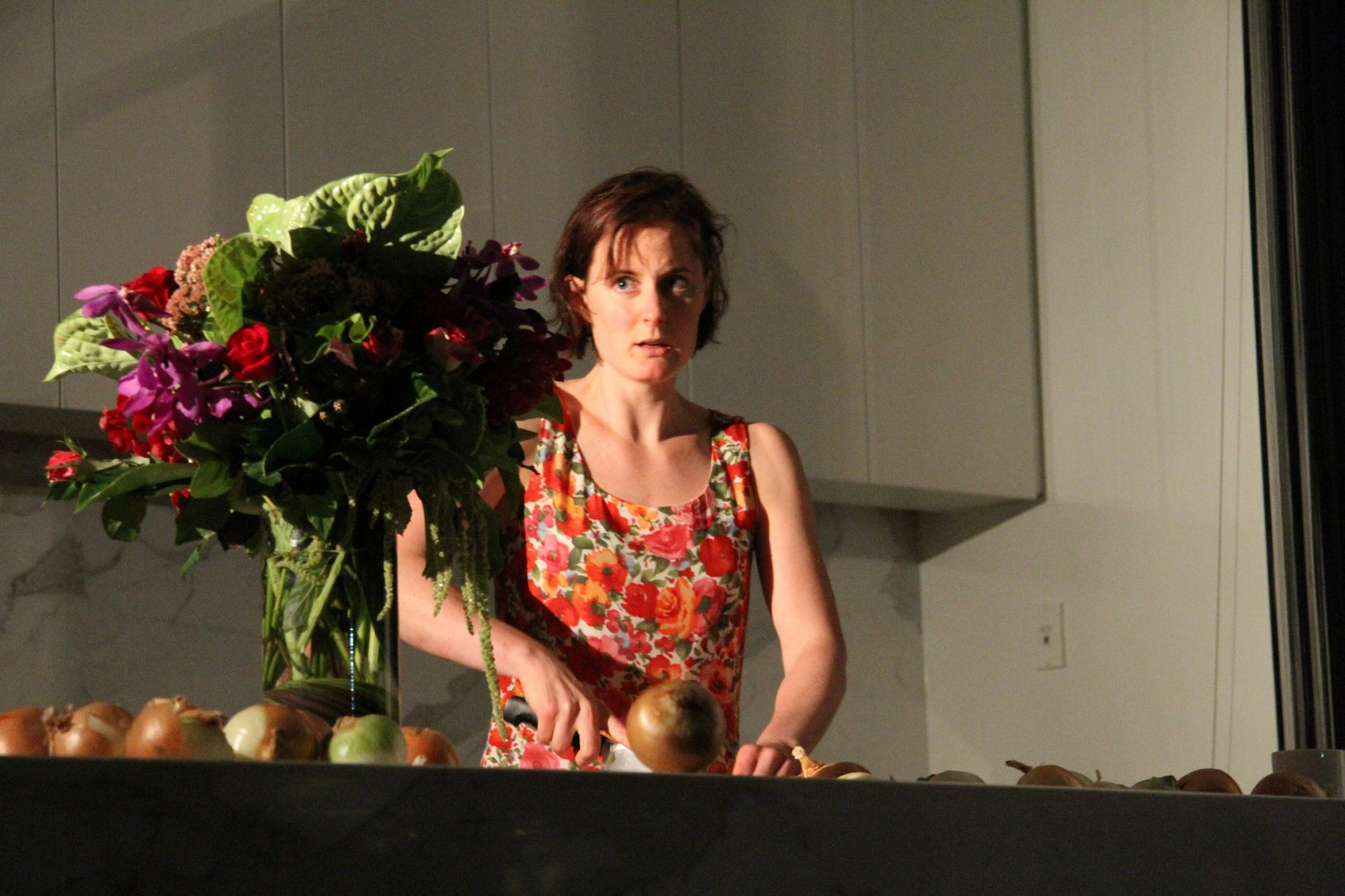 Shot from below of a woman chopping onions at a kitchen bench next to a vase of flowers