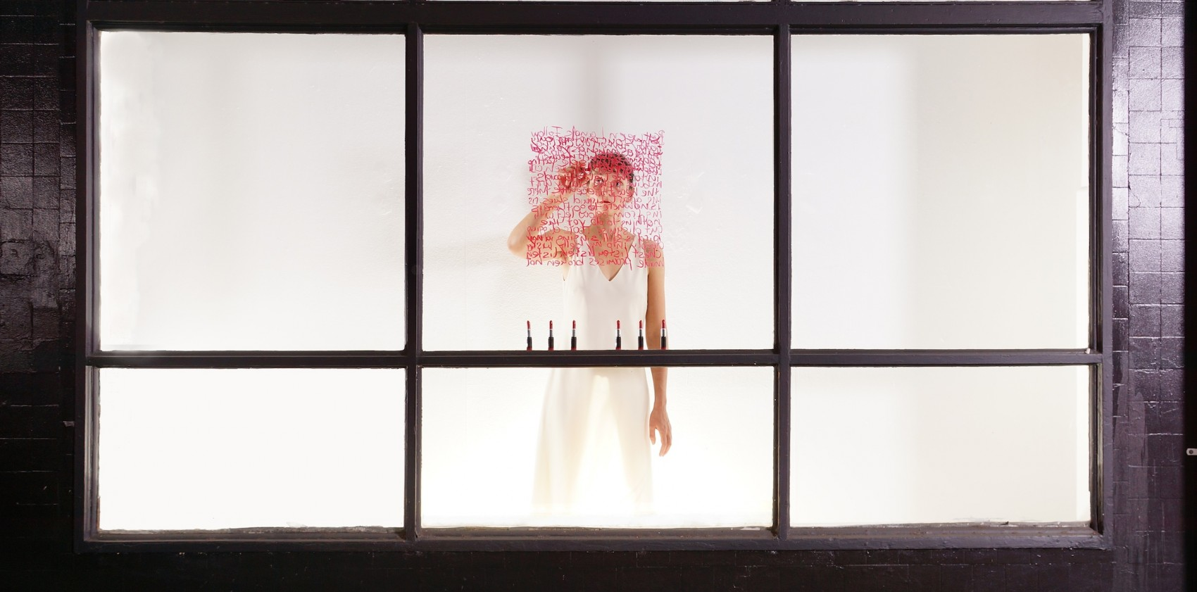 Looking through white windows with black frames to a woman wearing white who is writing in red on the glass