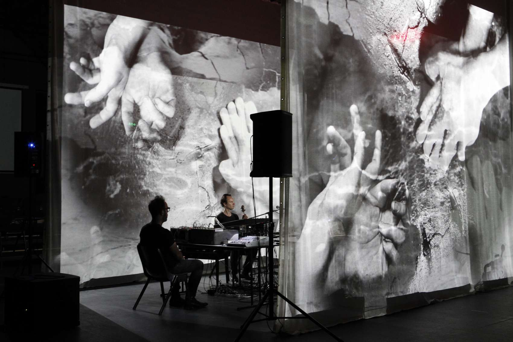 Two seated performers between large screens with projections of hands