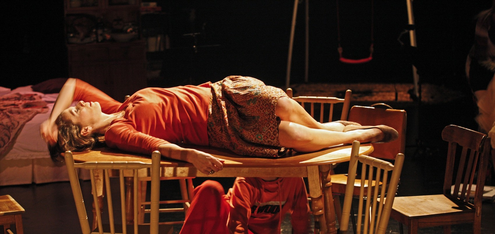Stage image of a woman lying on top of a wooden table, chairs around