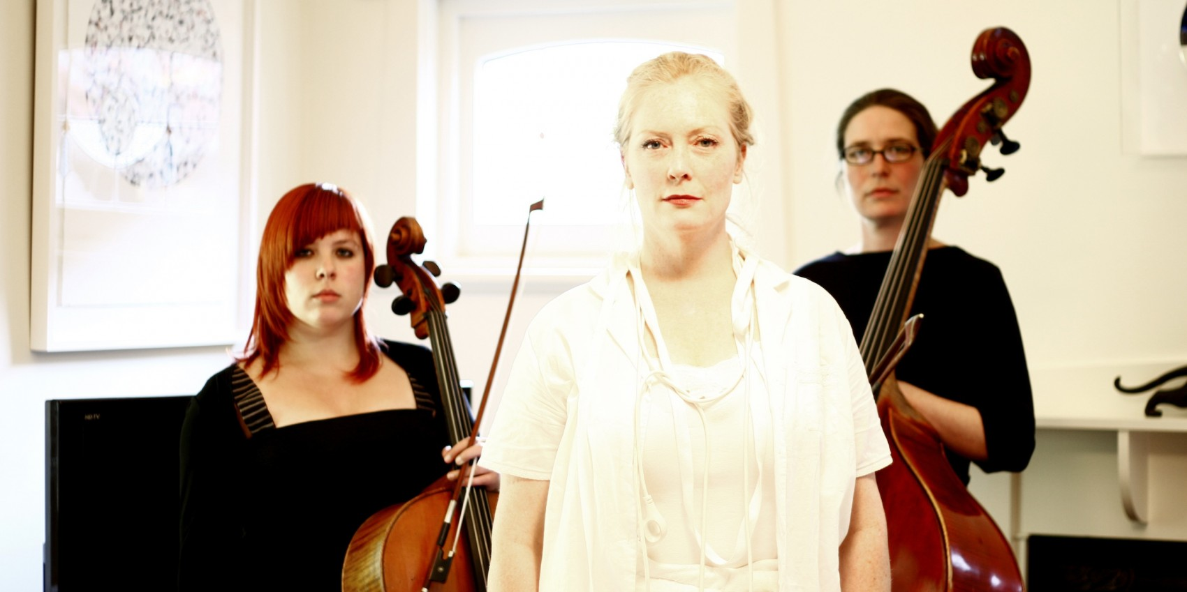 Three women stand in a white room, one wearing white, the other two wearing black, one holds a cello and one a double bass