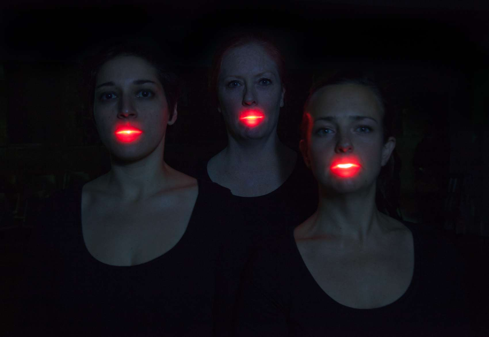 Head and shoulders of three women with illuminated mouths against a dark background