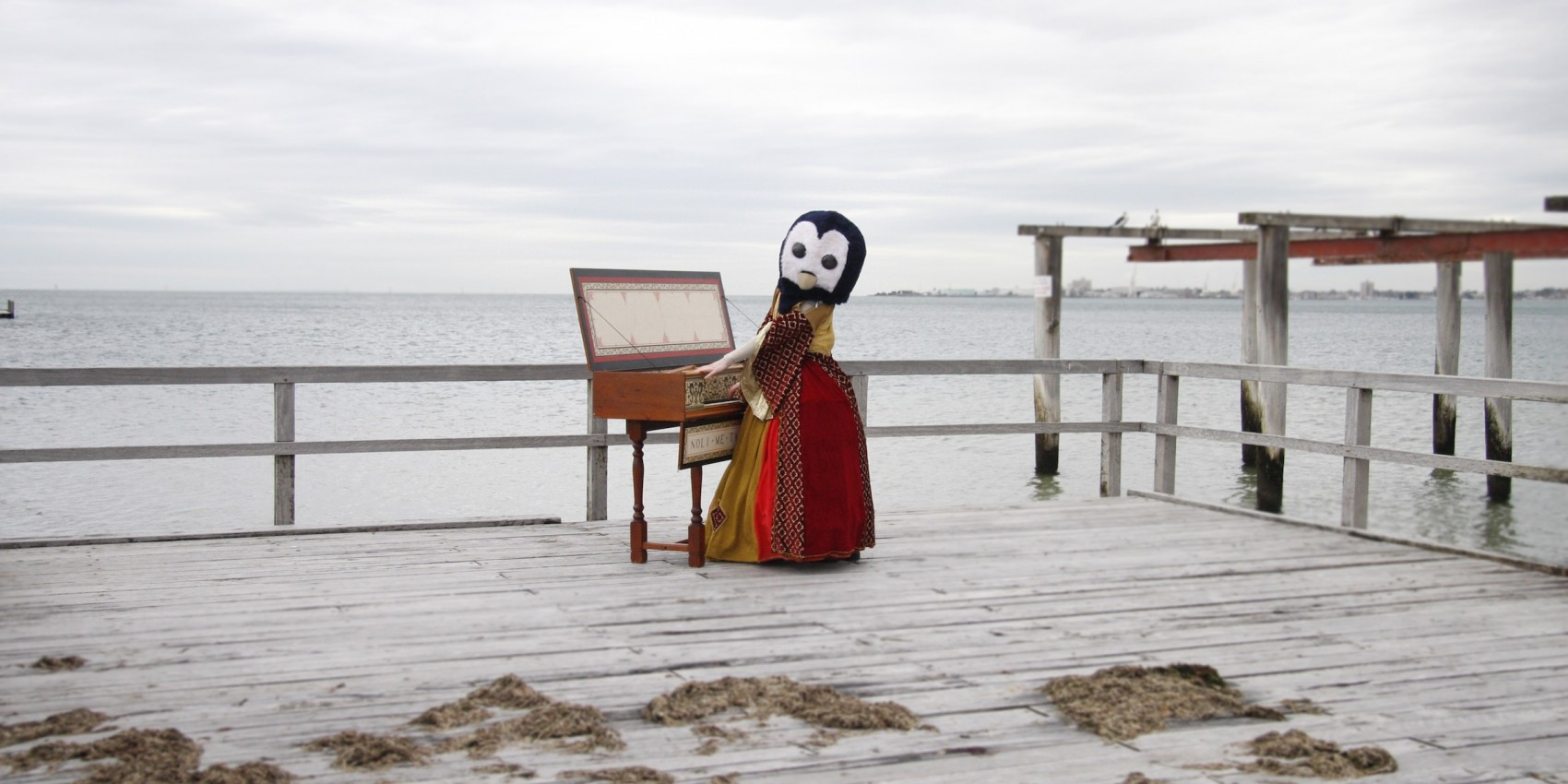 A pier at a beach on which is placed a person in elaborate costume, a large penguin mask, playing an old-fashioned keyboard