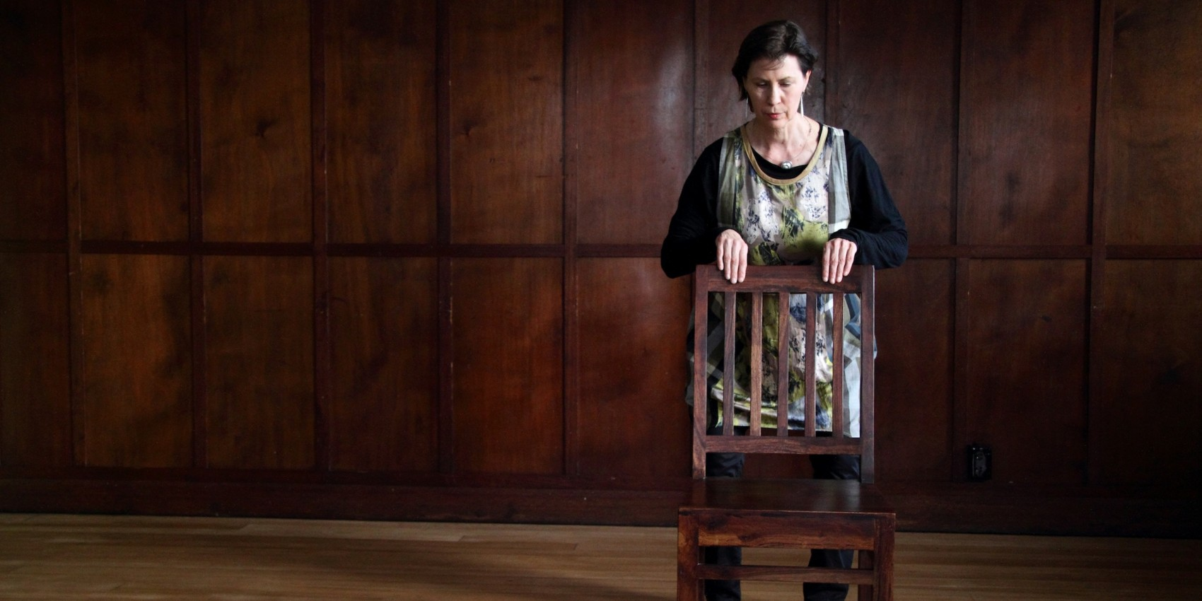 Promo image of a woman standing behind a wooden chair