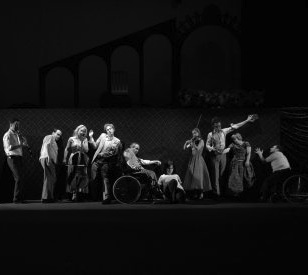 Production image: long shot of a group of ten people on a stage in various poses