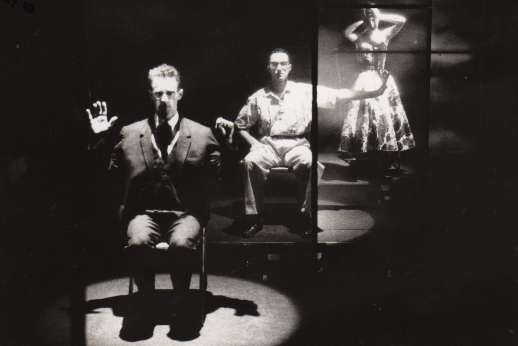 Production image of two men seated in spotlights and one woman standing, arms raised