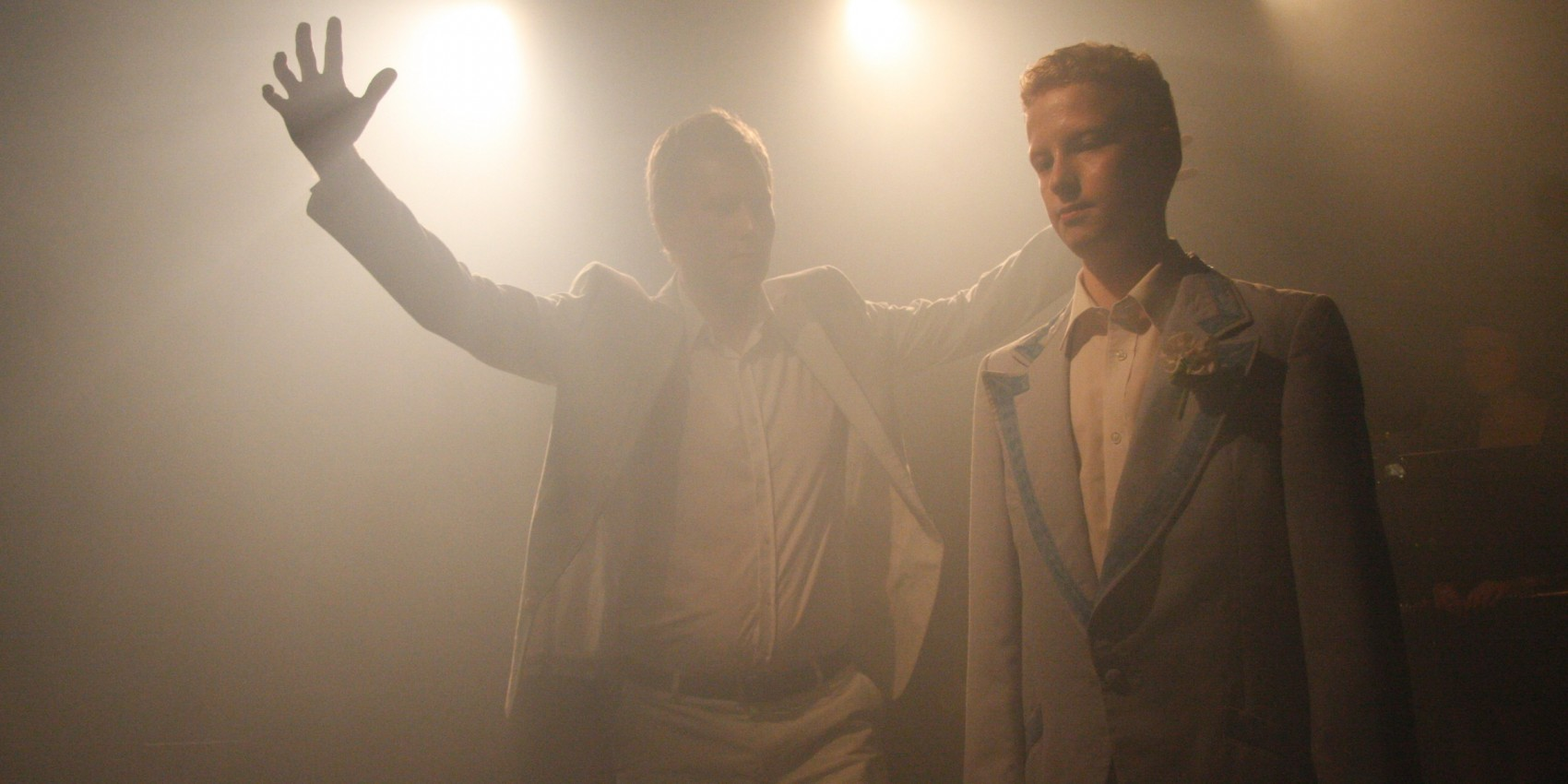 Production image of two men in grey suits one with arms raised both under hazy light of spotlights
