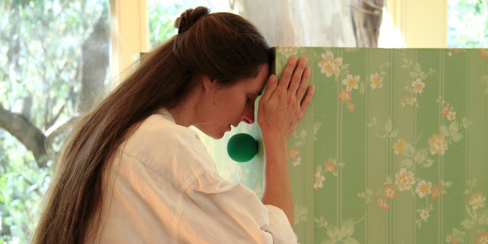 Woman with her head pressed against a pale green floral patterned box