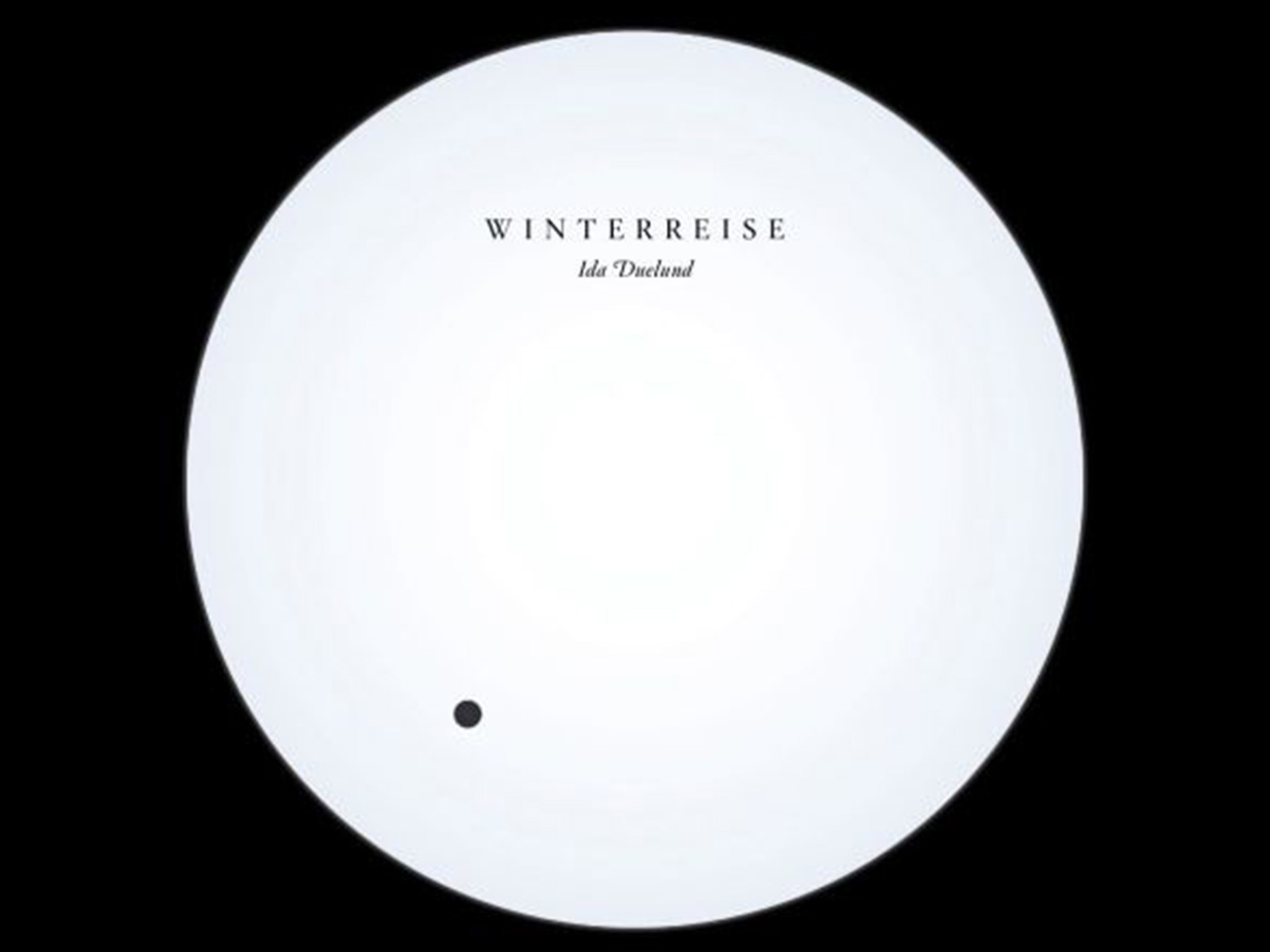 Promo image: a white circle with the words Winterreise Ida Dueland on it set against a black background