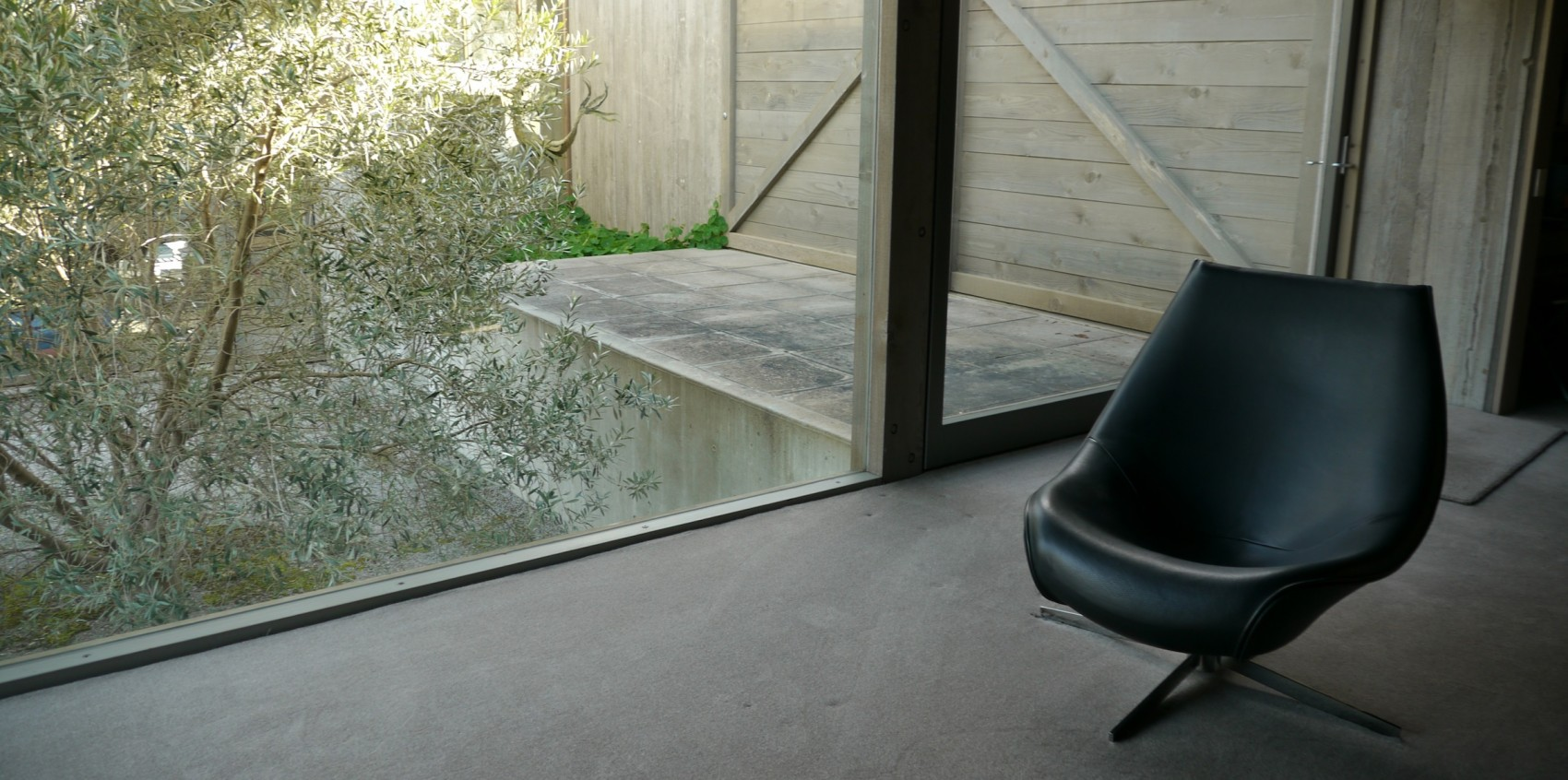 A black chair on a grey floor next to a window where tree foliage is visible