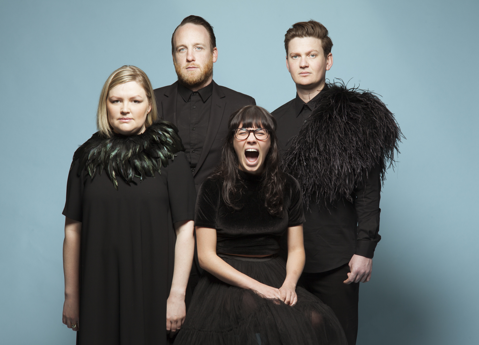 Four performers against a blue background, one is yelling