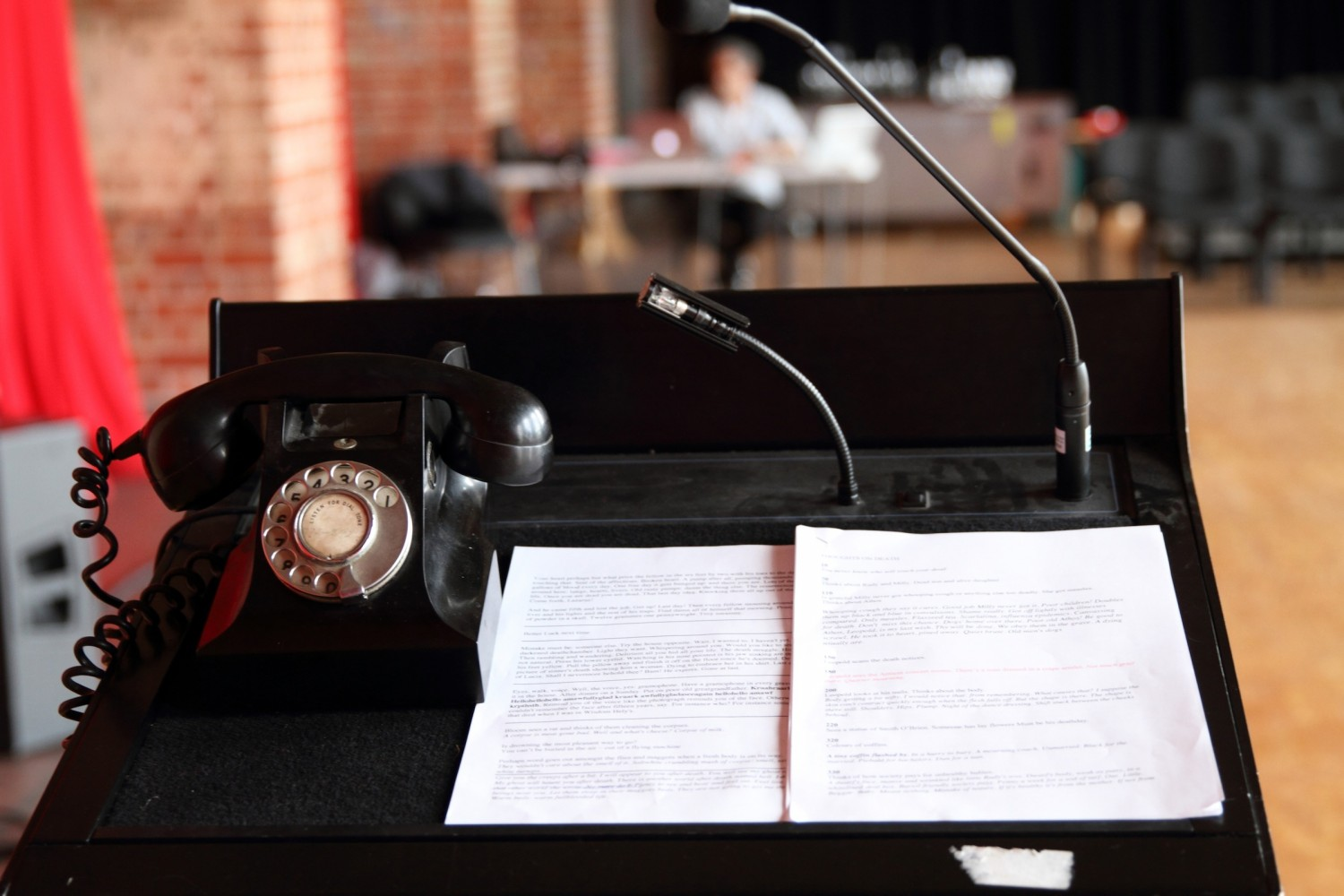 Old fashioned black telephone on stand with papers against a blurred room background