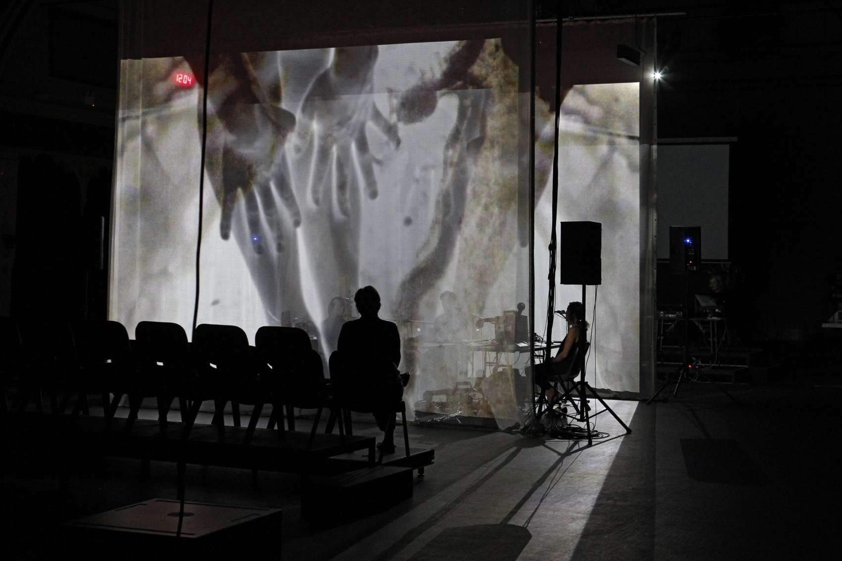 Shot of empty seating bank and two performers seated with large screens on which images of hands are projected