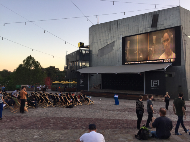 People and deck chairs in open courtyard in front of large screen at Federation Square Melbourne