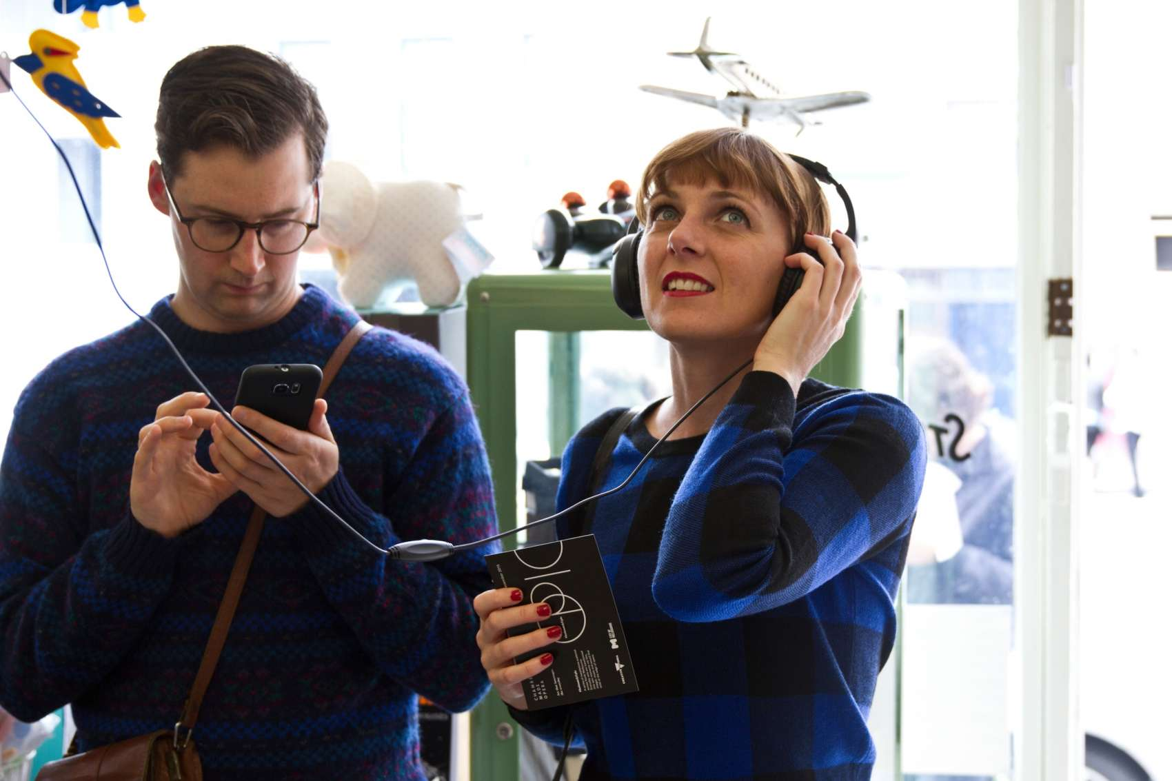 Man checking phone and woman wearing headphones in a toy shop