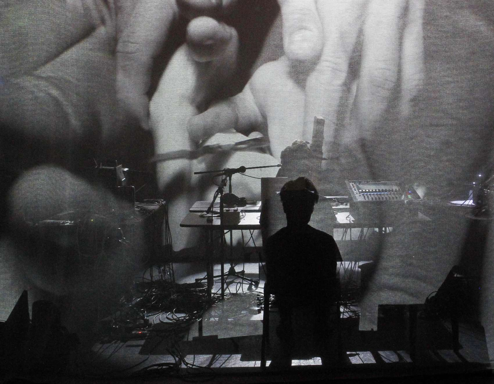 Image of a performer and equipment against a large screen projection of intertwined hands