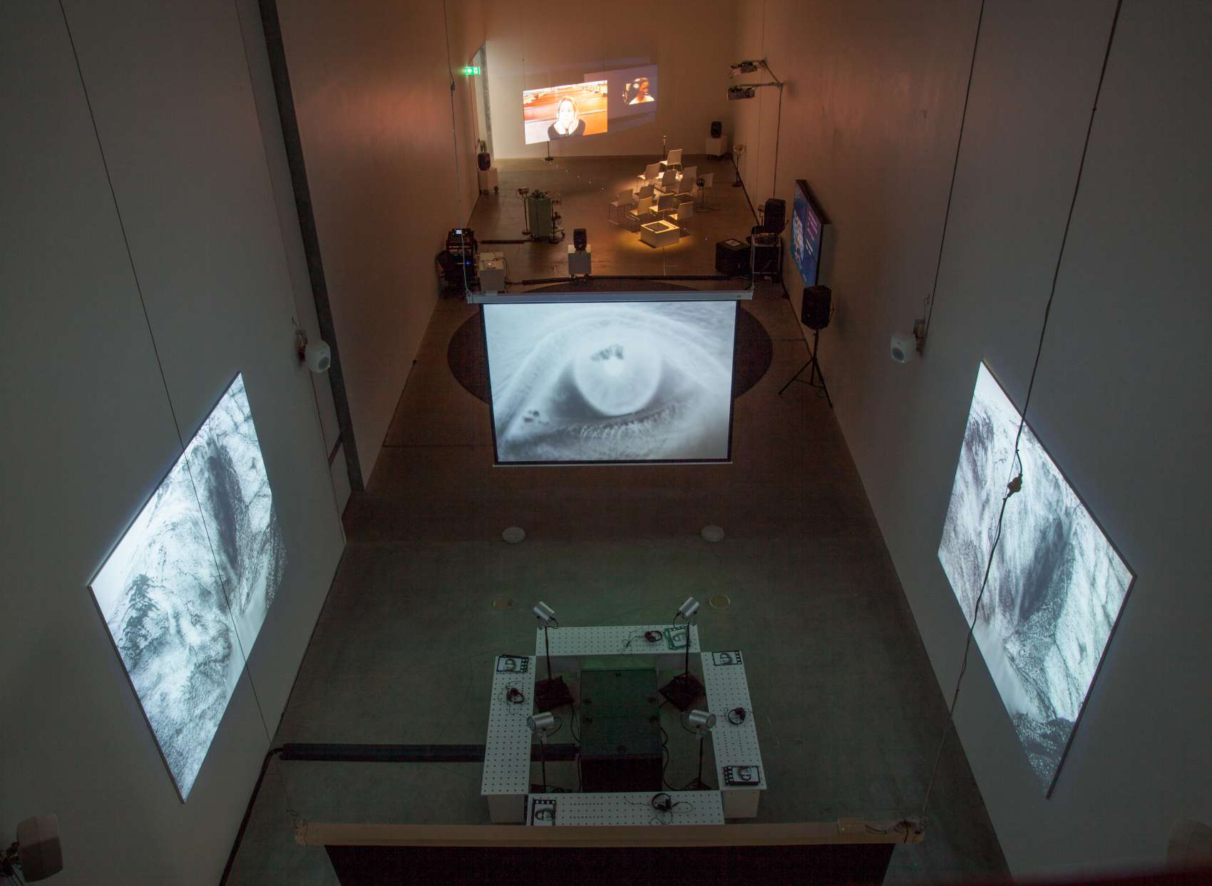 An arial view of an exhibition with screens and headphones.