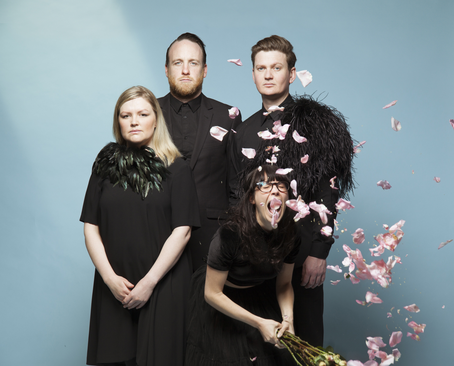 Four performers against a blue background, one is yelling and throwing rose petals