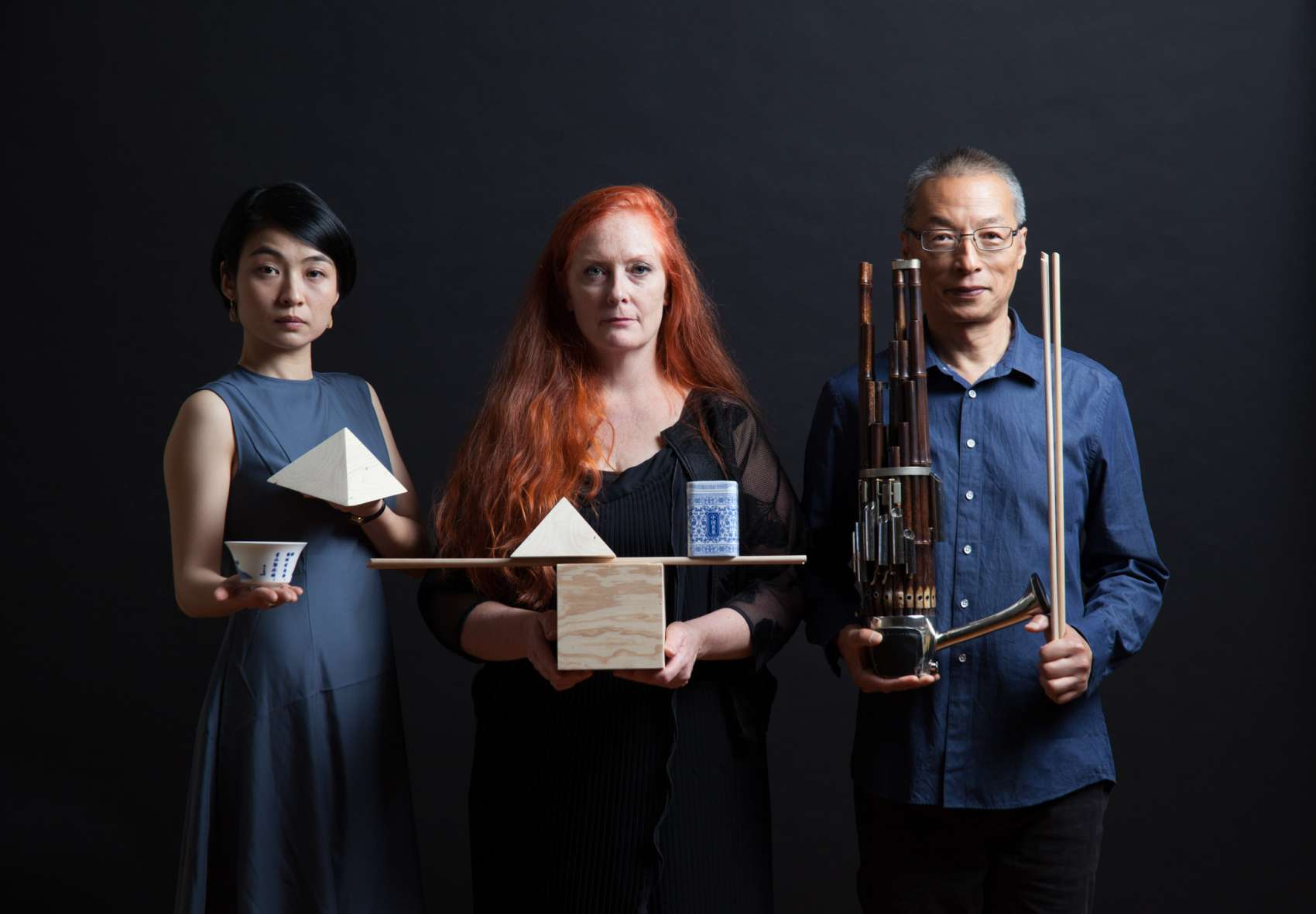 Three performers holding geometric objects and musical instruments.