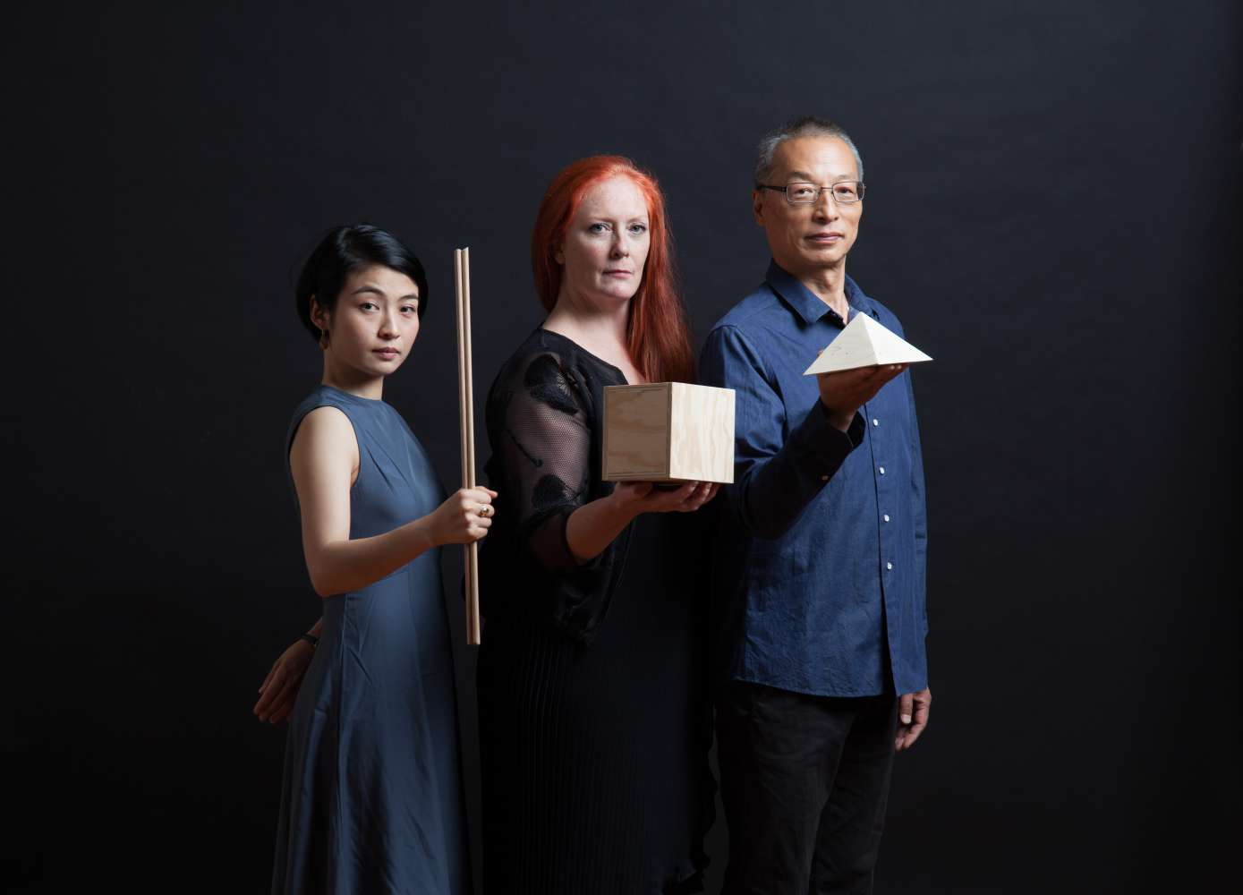 Three performers holding wooden objects standing against a black background