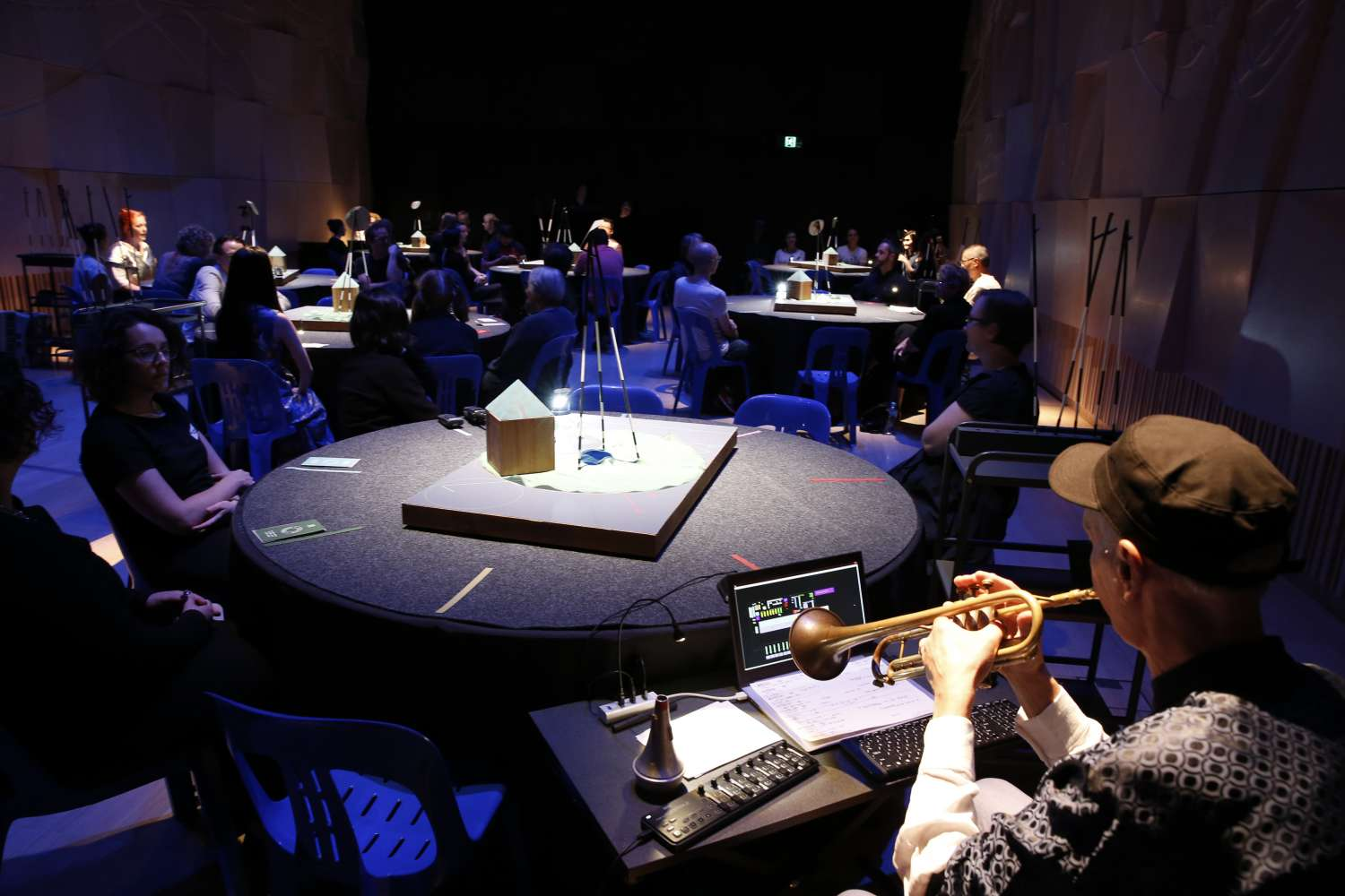 A performance space with audience seated around round tables
