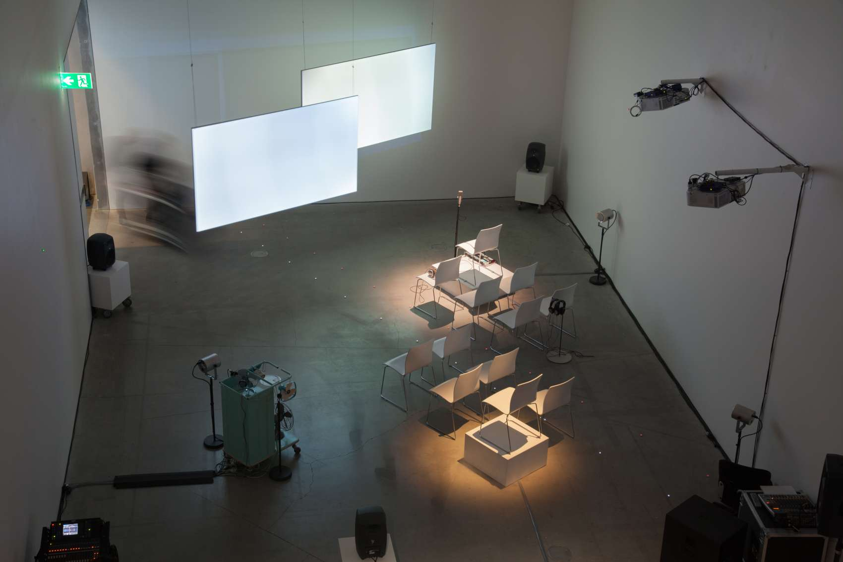 Birds eye view of empty performance space with chairs and screens