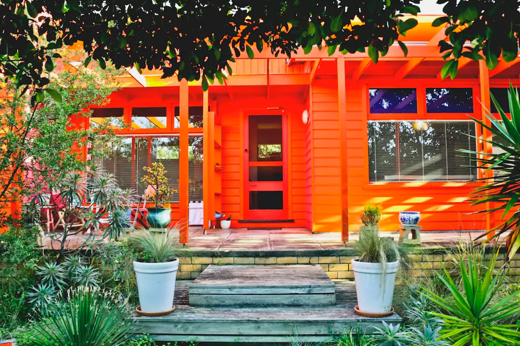 Front of bright orange house surrounded by green foliage