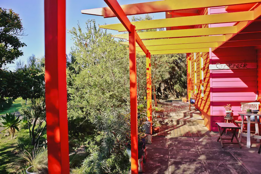 Sunlight shining on a red and yellow painted porch and garden