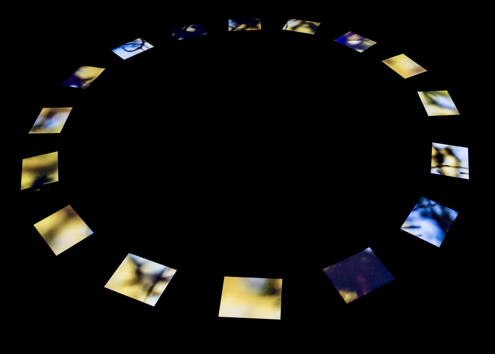 Black image with brightly lit iPad screens in a circle